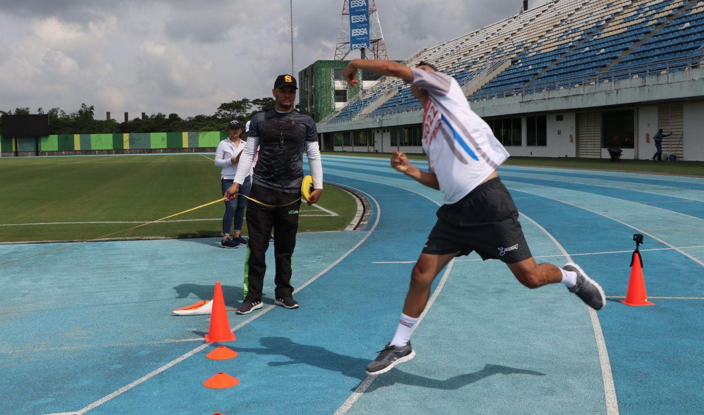 Persona con discapacidad física esta realizando un lanzamiento de bala, al fondo se ve el escenario deportivo, el juez y dos personas del staff. Foto tomada en Barrancabermeja - Santander, 2019.