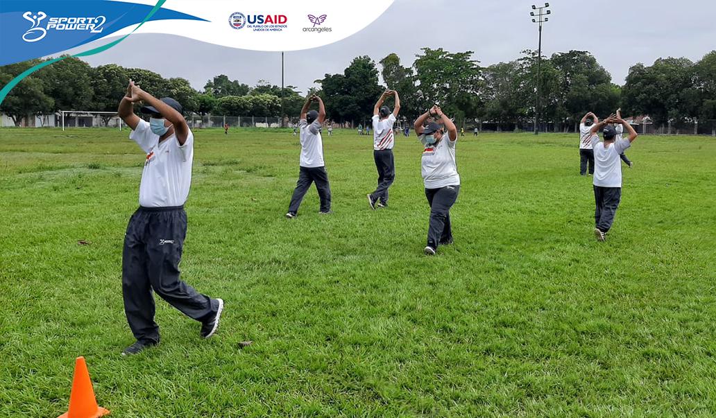 deportistas con discapacidad del proyecto realizan un entrenamiento rodeando conos sobre un escenario en cesped.