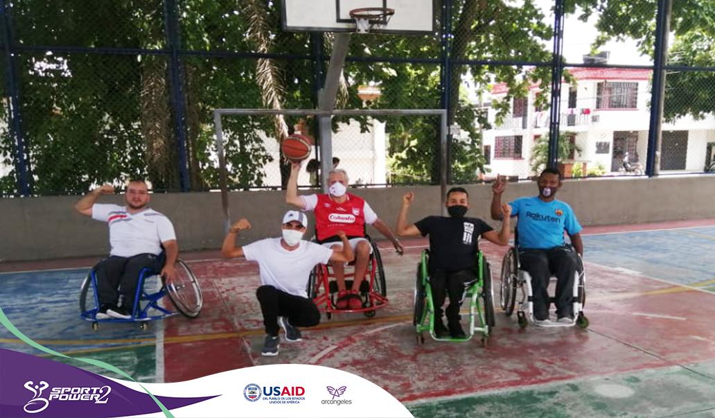 Cuatro deportistas con discapacidad física del equipo de baloncesto en silla de ruedas del caqueta posan haciendo la seña del proyecto, están ubicados en una cancha de baloncesto.