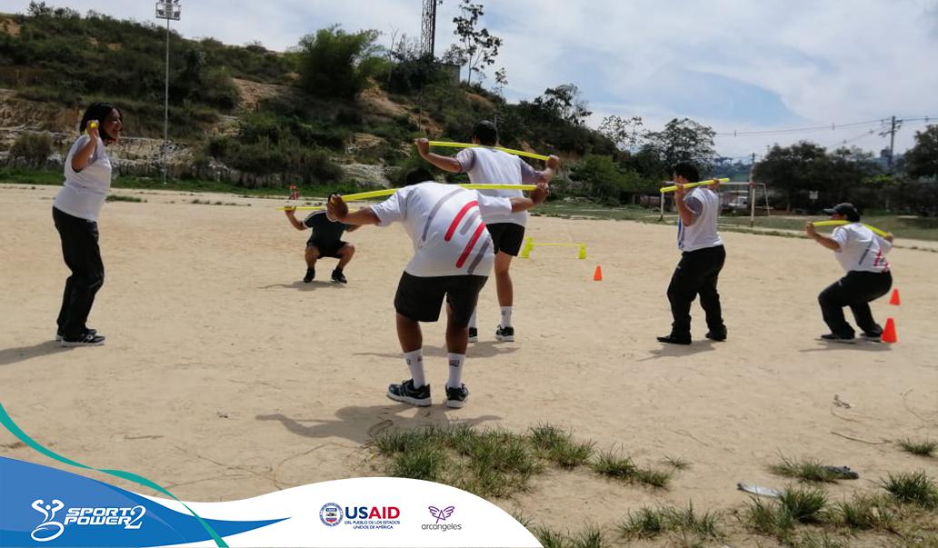 5 Deportistas con discapacidad del proyecto están realizando su entrenamiento en un escenario con arena, al fondo se bica su entrenador brindando las indicaciones del ejercicio.
