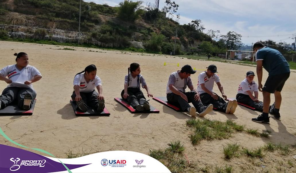 Seis deportistas del proyecto estan sentados sobre colchonetas en una escenario con arena en fila, al final de esta se encuentra su entrenador dando instrucción a la primera persona.