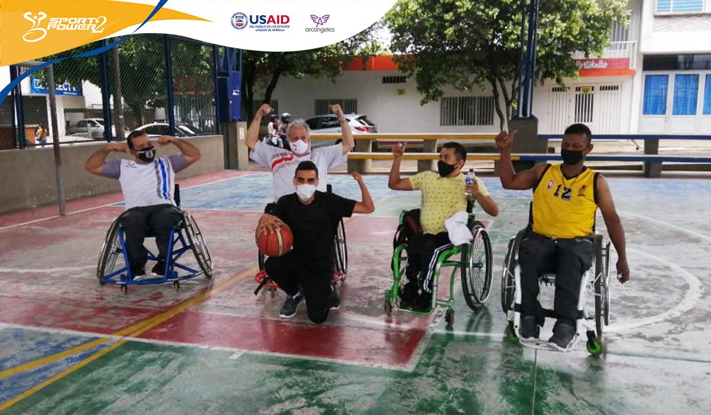 Tres deportistas con discapacidad física del equipo de baloncesto en silla de ruedas del caqueta posan haciendo la seña del proyecto, en la mitad se ubica el profesional psicosocial de Caqueta.