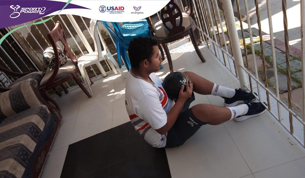 Deportista sentado realizando ejercicios con un balon, esta sentado en un tapate y en un lugar de su casa.