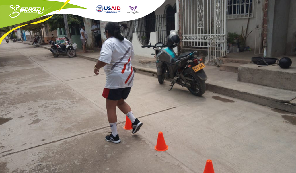 Una deportista realiza su ejercicio en la calle, esta trotando alrededor de tres conos.